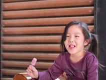 Little Asian girl eating ice cream. Wood shade stripes background Stock Photo
