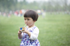 Little Asian girl eats yoghourt in park Royalty Free Stock Photos