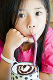 Little asian girl enjoy a cup of chocolate shake. Royalty Free Stock Images