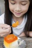 Little Asian girl enjoy orange cheese pie. Royalty Free Stock Image