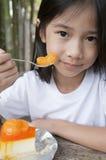 Little Asian girl enjoy orange cheese pie. Stock Image