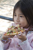 Little Asian girl enjoy pizza. Stock Images