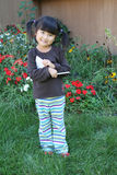 Little asian girl in garden taking notes stock photography