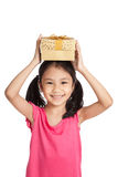 Little asian girl with gift box over her head Stock Images