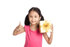 Little asian girl with gift box show thumbs up Stock Image