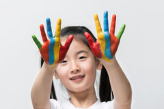 Little Asian girl with hands painted in colorful paints.  stock photography