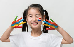 Little Asian girl with hands painted in colorful paints. Little Asian girl with hands painted in colorful paints royalty free stock photography