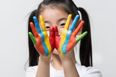 Little Asian girl with hands painted in colorful paints. Little Asian girl with hands painted in colorful paints stock photo
