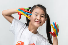 Little Asian girl with hands painted in colorful paints.  royalty free stock photo