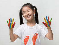Little Asian girl with hands painted in colorful paints. Stock Images