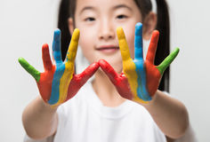 Little Asian girl with hands painted in colorful paints. Royalty Free Stock Image