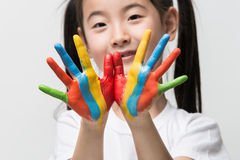 Little Asian girl with hands painted in colorful paints. Royalty Free Stock Photos