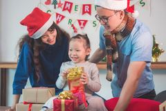 Little girl and her parents open christmas gift boxes Stock Photos