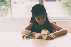 Little asian girl hold little house with money stack - money sav Royalty Free Stock Image