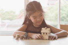 Little asian girl hold little house with money stack - money sav Royalty Free Stock Images