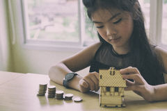 Little asian girl hold little house with money stack - money sav Stock Images
