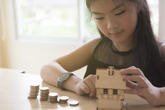 Little asian girl hold little house with money stack - money sav Royalty Free Stock Photos