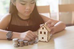 Little asian girl hold little house with money stack - money sav Stock Image