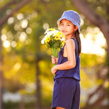 Little Asian Girl Holding A Bunch Of Flowers Royalty Free Stock Image