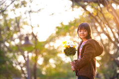 Little asian girl holding a bunch of flowers Stock Image