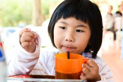Little Asian Girl holding glass for drink Royalty Free Stock Photo