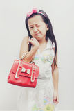 Little asian girl holding a red handbags. Stock Photo