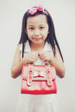 Little asian girl holding a red handbags. Stock Image