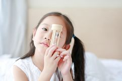 Little Asian girl holding sandglass in hand with looking through camera. Waiting times with hourglass stock photos