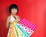 Little Asian girl holding shopping bags Stock Images