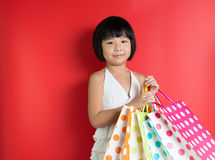 Little Asian girl holding shopping bags Royalty Free Stock Photography