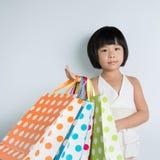 Little Asian girl holding shopping bags Stock Photos
