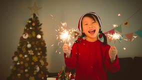 Girl holding sparkle firework and smile in room at Christmas night stock images