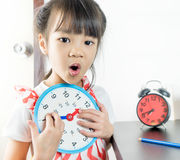 Little asian girl holding toy clock school time. Little asian girl holding toy clock for school time Stock Images