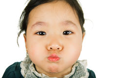 Little Asian girl inflates cheeks. Little Asian girl inflates cheeks, isolated on white background. Close-up Stock Photo