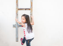 Little Asian girl kid climbs the stairs - Fire escape Stock Images