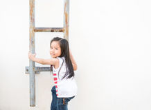 Little Asian girl kid climbs the stairs - Fire escape Royalty Free Stock Photo