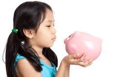 Little asian girl kiss a piggy bank Stock Photos