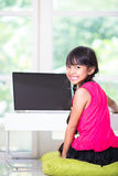 Little asian girl with a laptop computer Royalty Free Stock Images