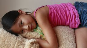 Little asian girl laying on a stuffed dog Stock Images
