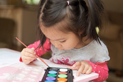 Little Asian girl learning to paint Royalty Free Stock Images