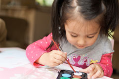 Little Asian girl learning to paint Stock Photography