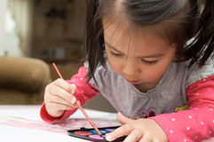 Little Asian girl learning to paint Stock Photos