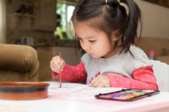 Little Asian girl learning to paint Stock Images