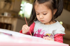 Little Asian girl learning to paint Royalty Free Stock Photography