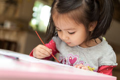 Little Asian girl learning to paint Royalty Free Stock Photos