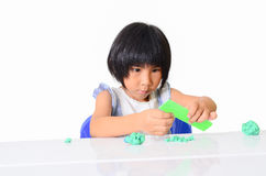 Little Asian girl is learning to use play dough. In a well lit room isolated on white Stock Photo