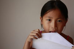 Little asian girl licking a envelope Royalty Free Stock Photo