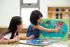 Little asian girl looking South east asia for play jigsaw stock image