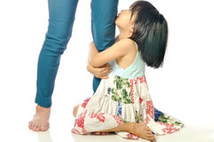 Little asian girl looking up and holding her mother leg Stock Images