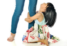 Little asian girl looking up and holding her mother leg. On white background Royalty Free Stock Photos